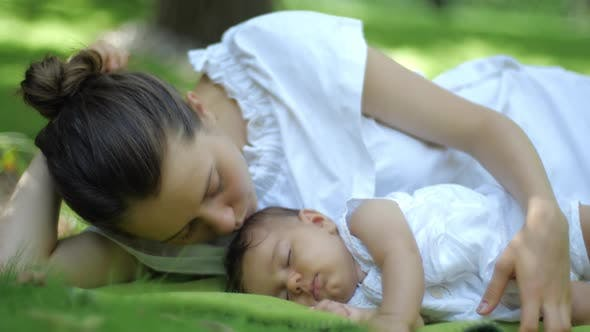 Mother Kisses Her Baby Sleeping on a Green Grass Outdoors. Happy Smiling Young Mother and Child in