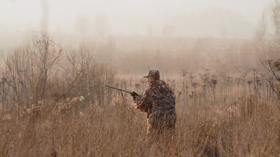 Thumbnail for Hunter in Hunting Equipment With a Rifle in His Hands Sneaks Through the Dry Grass to the Target