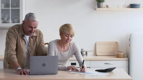Happy MiddleAged Spouses Calculating House Expenses And Bills At Home