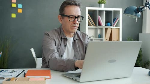 Mature Employee Working with Laptop Typing Sitting at Desk in Workplace