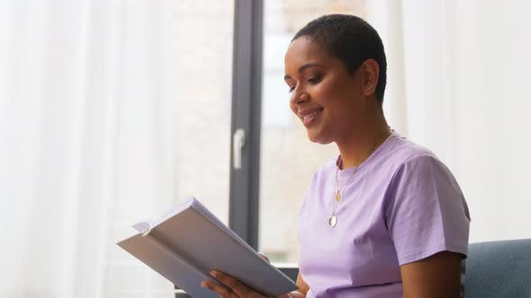Thumbnail for Happy African American Woman Reading Book at Home