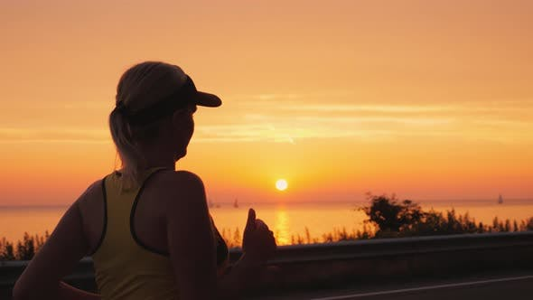 Cover Image for Athletic Young Woman Jogging Near the Sea Where the Sun Sets. Steadicam Shot
