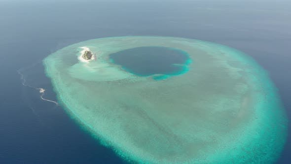Aerial: Flying over idyllic atoll, scenic travel destination in Indonesia