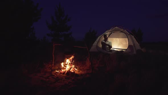 Thumbnail for A Man Rests in a Tent Near a Fire