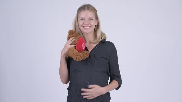 Young Happy Pregnant Businesswoman Hugging Teddy Bear