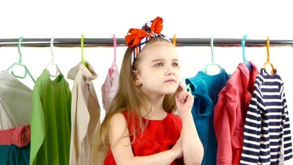 Thumbnail for Little Girl at the Store Chooses To Itself Clothes. White Background