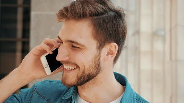 Handsome smiling man in casual clothes while having telephone conversation