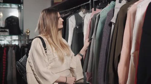 a Pretty Woman Looks at a Warm Cardigan That Is Found in a Modern Boutique