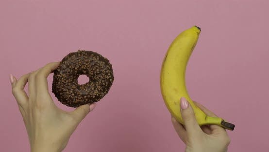 Thumbnail for Hands Holds Donut and Banana. Choice Donut Against Banana. Healthy or Junk Food