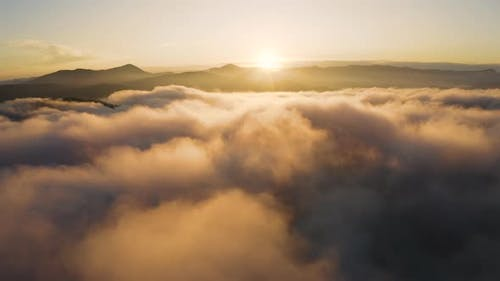 Aerial drone view of Sunrise over clouds. Flying above morning Fog in the Mountains.
