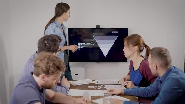 Cover Image for Young Woman Is Presenting Report for Her Colleagues at Business Meeting in Office Room, Showing Data