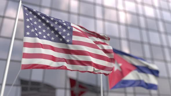 Waving Flags of the USA and Cuba Near Modern Skyscraper