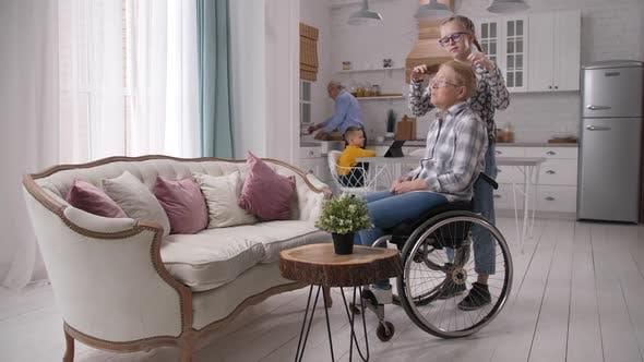 Loving Teen Granddaughter Combing Disabled Granny