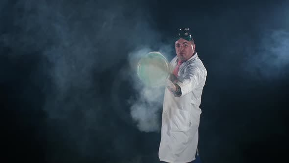 Thumbnail for Man Chemist in Uniform Making Interesting Trick with Air Smoke Bubble, Rounds on Black Background