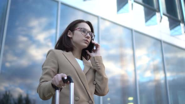 Thumbnail for A Young Woman Stands Against the Background of a Business Center and Speaks on the Phone. Girl