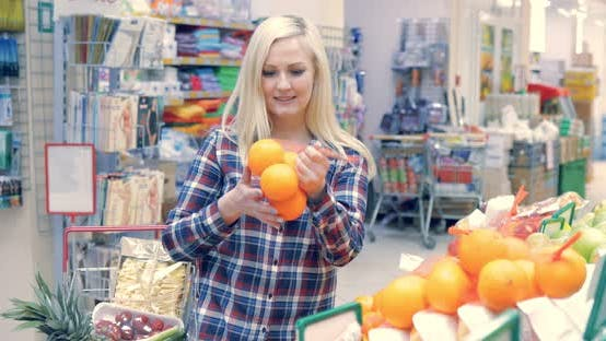 Young Woman Chooses Fruit in a Supermarket