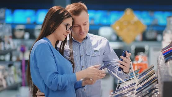 Thumbnail for Happy Couple Buying New Smart Phone in Tech Store. Deciding Which Model To Purchase.