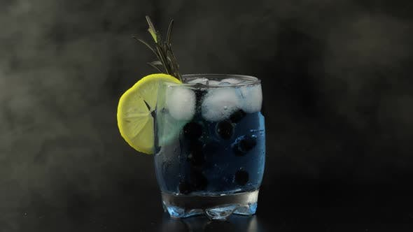 Thumbnail for Adding Black Currants in a Glass with Soda Lemonade Blue Cocktail