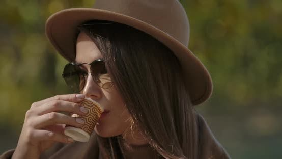 Cover Image for Close-up Face of an Elegant European Woman in Brown Hat and Sunglasses Drinking Tea or Coffee