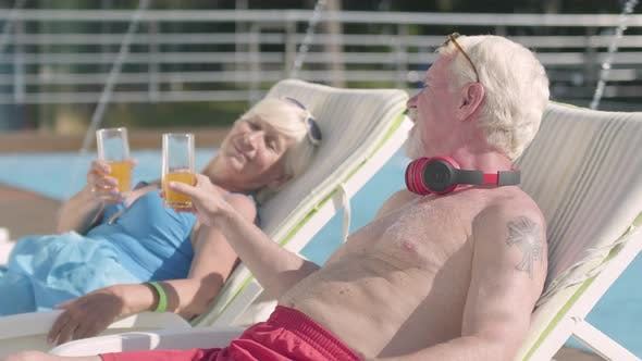 Cover Image for Mature Couple Lying on Sunbeds Near the Pool Drinking Juice, Talking and Smiling