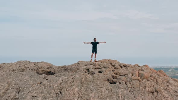 Young climber celebrates the top of the mountain with open arms