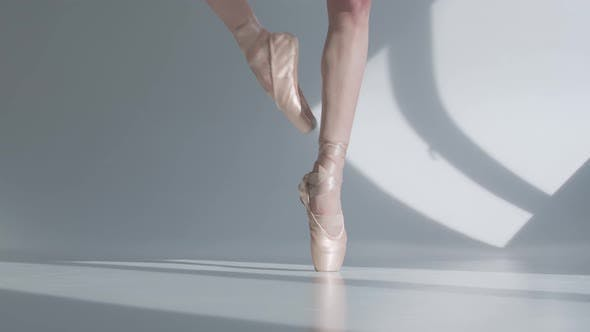 Thumbnail for Young Ballerina Dancing Ballet on the Tiptoes, Feet in Pointe Tied with Ribbons Closeup on White
