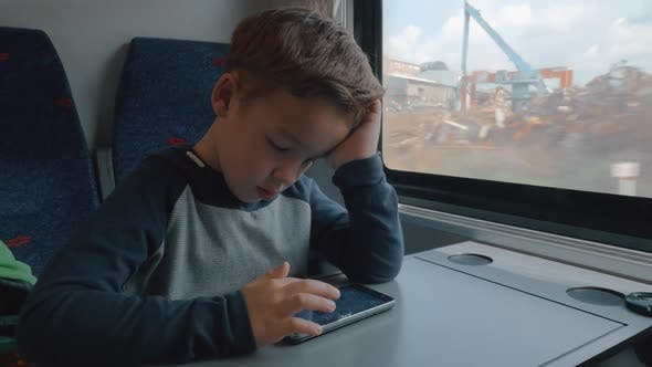Boy using cellphone in train passing by the dump