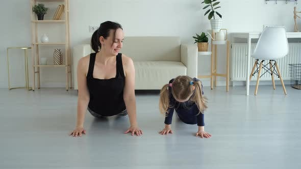 Little Girl with Mother Practicing Yoga Together