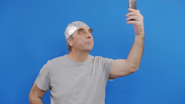 Frightened Man in a Tinfoil Hat Waved Off the 5G waves.5G Tower Radiation Protection. Irrational