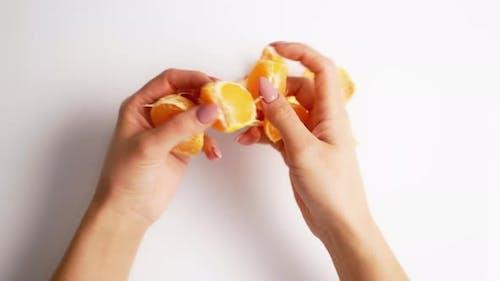 Peeled mandarin in female hands. Close up of mandarin on white background
