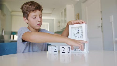 Boy Changing the Date on the Wooden Calendar on February 14 or Valentines Day