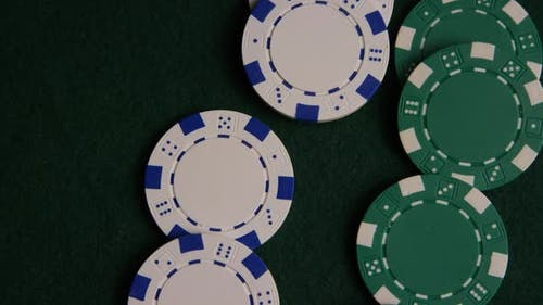 Rotating shot of poker cards and poker chips on a green felt surface - POKER 045