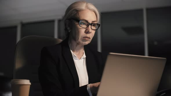 Thumbnail for Grey-Haired Corporate Employee Working Overtime in Dark Empty Office