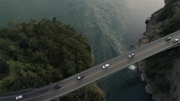 Thumbnail for Overhead Aerial Above Cars Traveling On High Canyon Bridge Crossing Blue Ocean Water