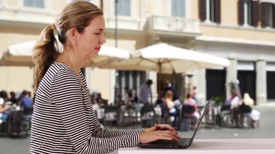 Thumbnail for Attractive Caucasian woman typing on laptop outside