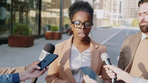 Black Businesswoman Giving Interview to Press on City Street