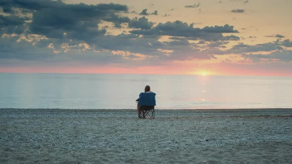 Thumbnail for Full Shot of Woman Admiring Sunset on the Sea Sitting in Folding Tourist Chair