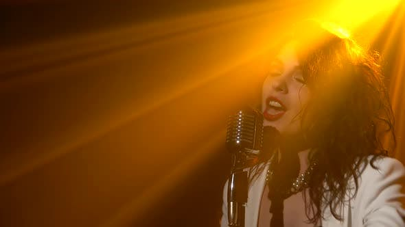 Thumbnail for A Stylish Girl Vocalist Sings on Stage in a Vintage Microphone. Dark Studio with Smoke and Neon