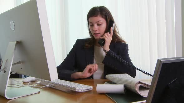 Thumbnail for Young business woman at desk with phone