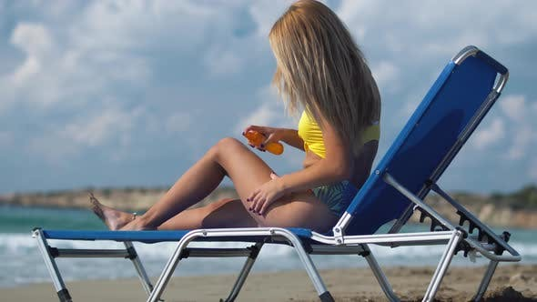 Thumbnail for Girl Is Lying on a Lounger on the Beach and Use a Sunburn Spray on Her Body To Not Get Burnt