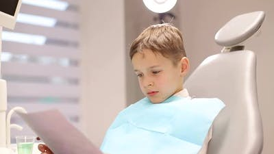 The child is afraid of the dentist, little boy visiting the dentist and looking scared