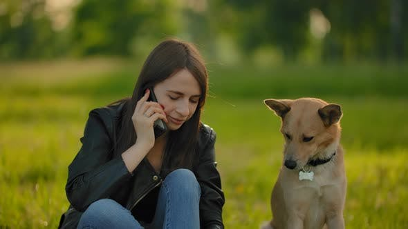 Thumbnail for Attractive Girl Talking on the Smartphone While Walking with a Dog in the Park.
