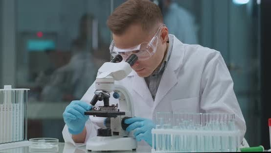 Genetic Engineer Is Exploring Analysis in Laboratory, Looking in Microscope, Experiments with DNA