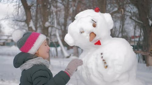 Girl Inserts a Nose on the Snowman