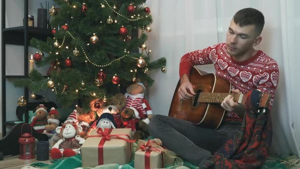 Thumbnail for Handsome man in red winter sweater is sitting on plaid near Christmas tree and playing guitar