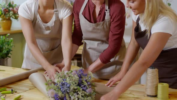 Thumbnail for Skilled florist teaching trainees bouquet wrapping