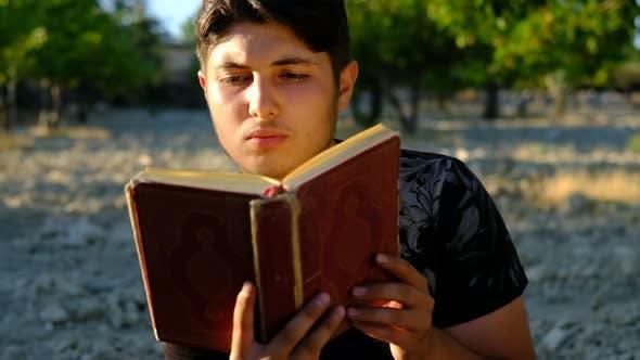 Young Man Reading Quran Outdoors