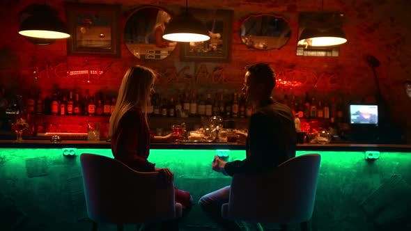 Thumbnail for An Attractive Couple Having a Date in the Bar - Sitting By Stand and Clinking Their Glasses - Cheers