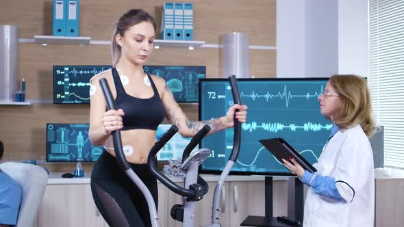Cover Image for Female Athlete Runs on Treadmill with Electrodes Attrached on Her Body