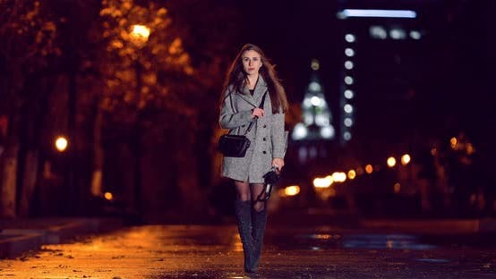 The Girl Goes with an Umbrella in the City in the Lights